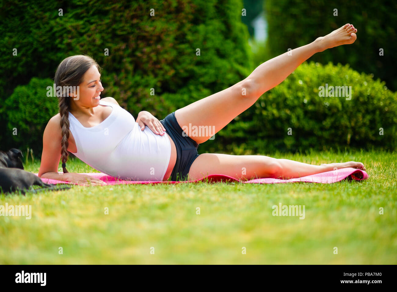 Pregnant woman performing side reclining leg lift while lying on yoga mat in park - Stock Image