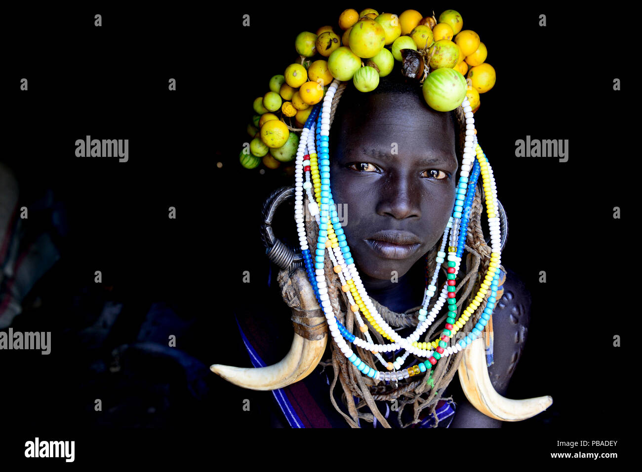 Young girl wearing traditional headdress. Mursi tribe, Mago National Park. Omo Valley, Ethiopia. - Stock Image