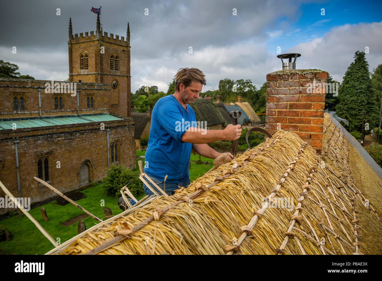 Dan Quatermain, master thatcher, working on a thatched roof in Wroxton village, Oxfordshire, UK. September 2015. - Stock Image
