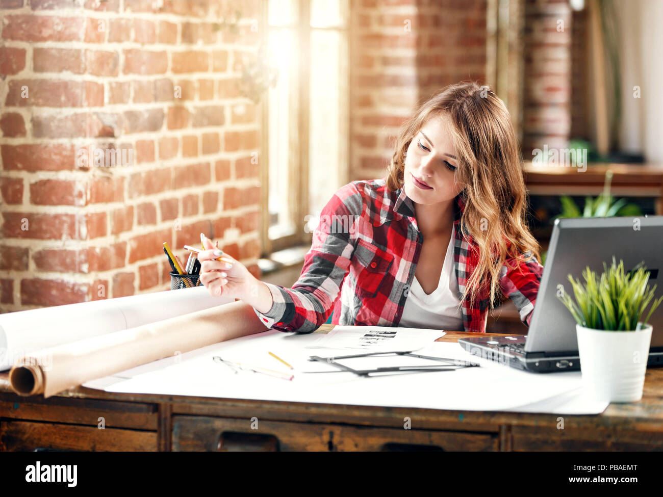 Pretty ambitious female architect in plaid shirt drawing a new project in loft office - Stock Image