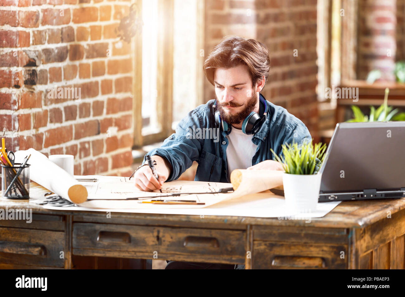 Concentrated young architect working with blueprint while sitting with laptop in a loft sunny office - Stock Image