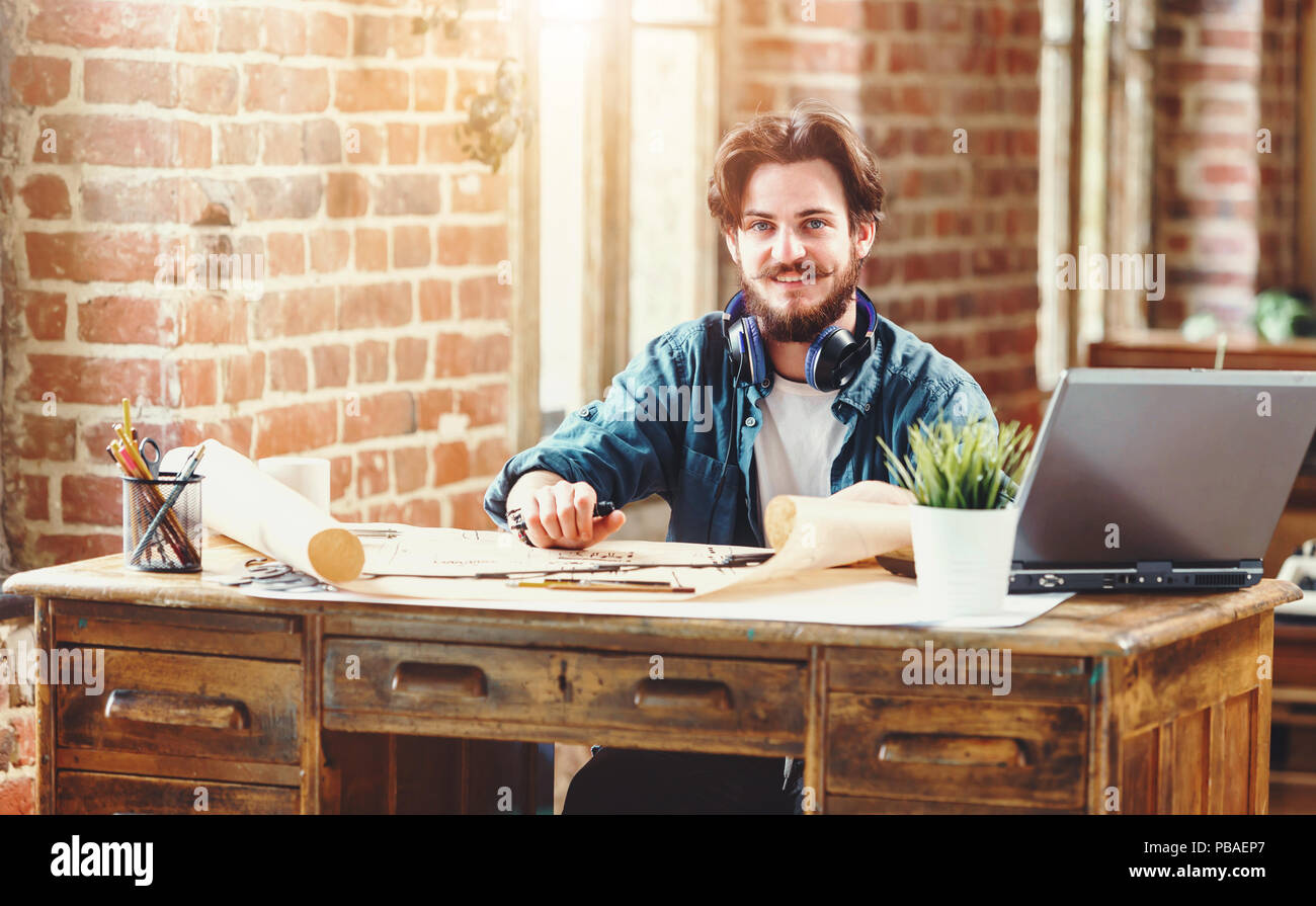Handsome bearded male architect working on a building plan at his desk smiling to the camera joyfully copyspace professionalism trustworthy qualified experienced engineer constructionist developer - Stock Image