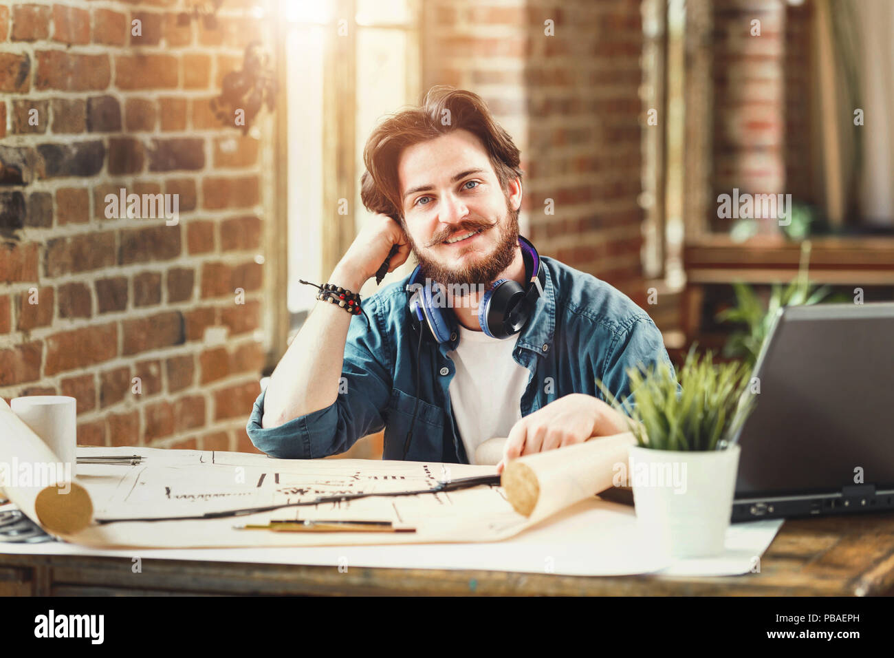 Male bearded architect smiling to the camera sitting at his desk at the office working on building plans copyspace creativity engineering project developing worker occupation career successful entrepreneur. - Stock Image