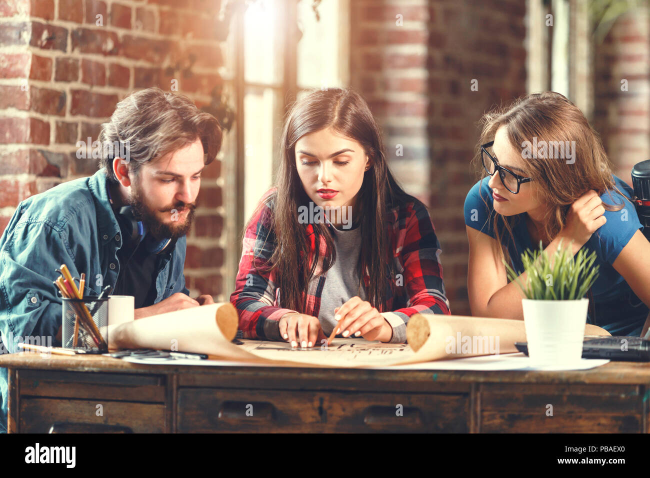 Crew of young professional designers discussing ideas about blueprint during meeting in the loft modern office - Stock Image
