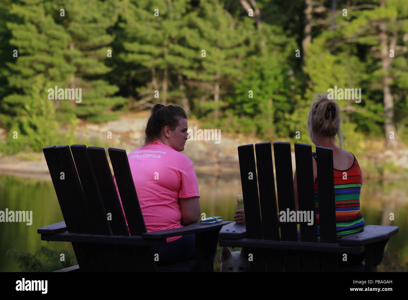 Pointe au baril, Canada - July 21st 2018: A pair of women sit in Muskoka style chairs and talk by the lake. Canadian cottage country brings in millions of tourists every year.. - Stock Image