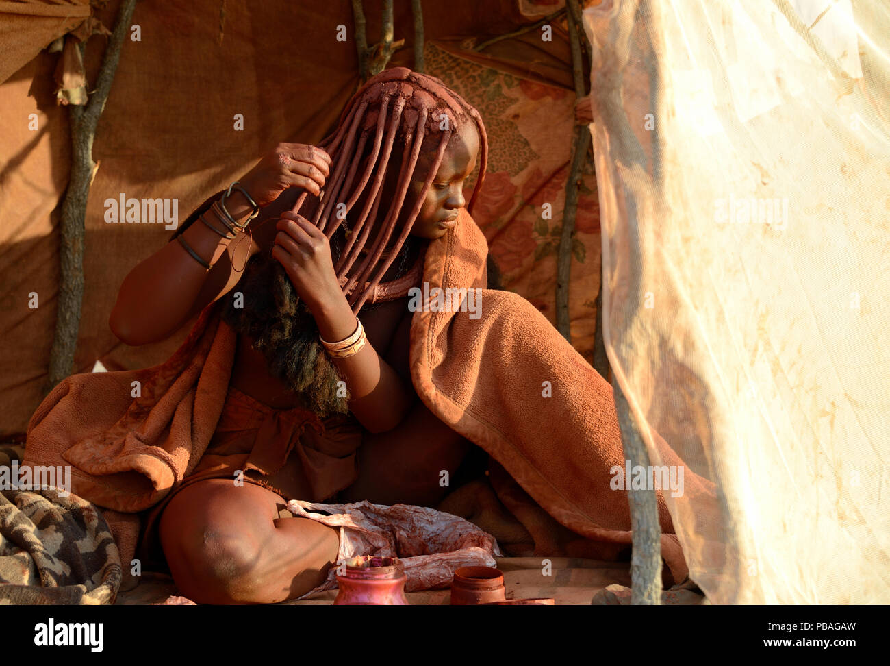 Himba woman applying Otjize (a mixture of butter, ochre and ash) to her hair. Marienfluss Valley. Kaokoland, Namibia October 2015 - Stock Image