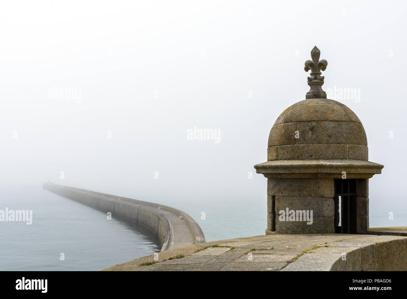 The long breakwater of the walled city of Saint-Malo in Brittany, France, seen from the ramparts in foggy weather with a turret in the foreground. - Stock Image