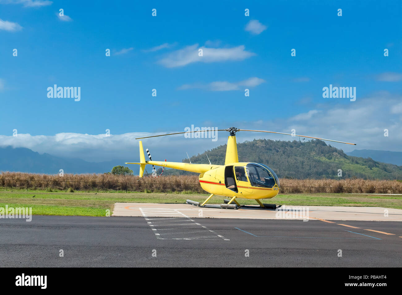 Yellow Sightseeing Helicopter Parked in a deserted meadow in a Hawaiian Island - Stock Image