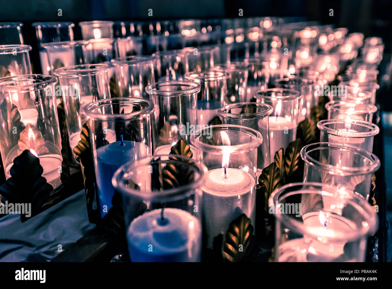 Closeup side pattern of many white, blue religious votive candles with yellow, purple flame in church or cathedral - Stock Image