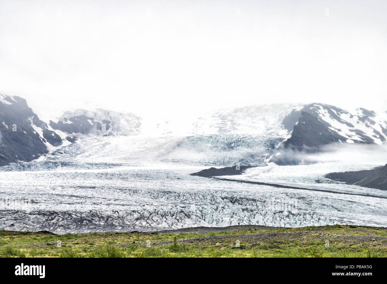 View on Skaftafell National Park, Iceland glacier ice tongues with people in distance, rocks, moss, fog, clouds, cliffs, mountains - Stock Image