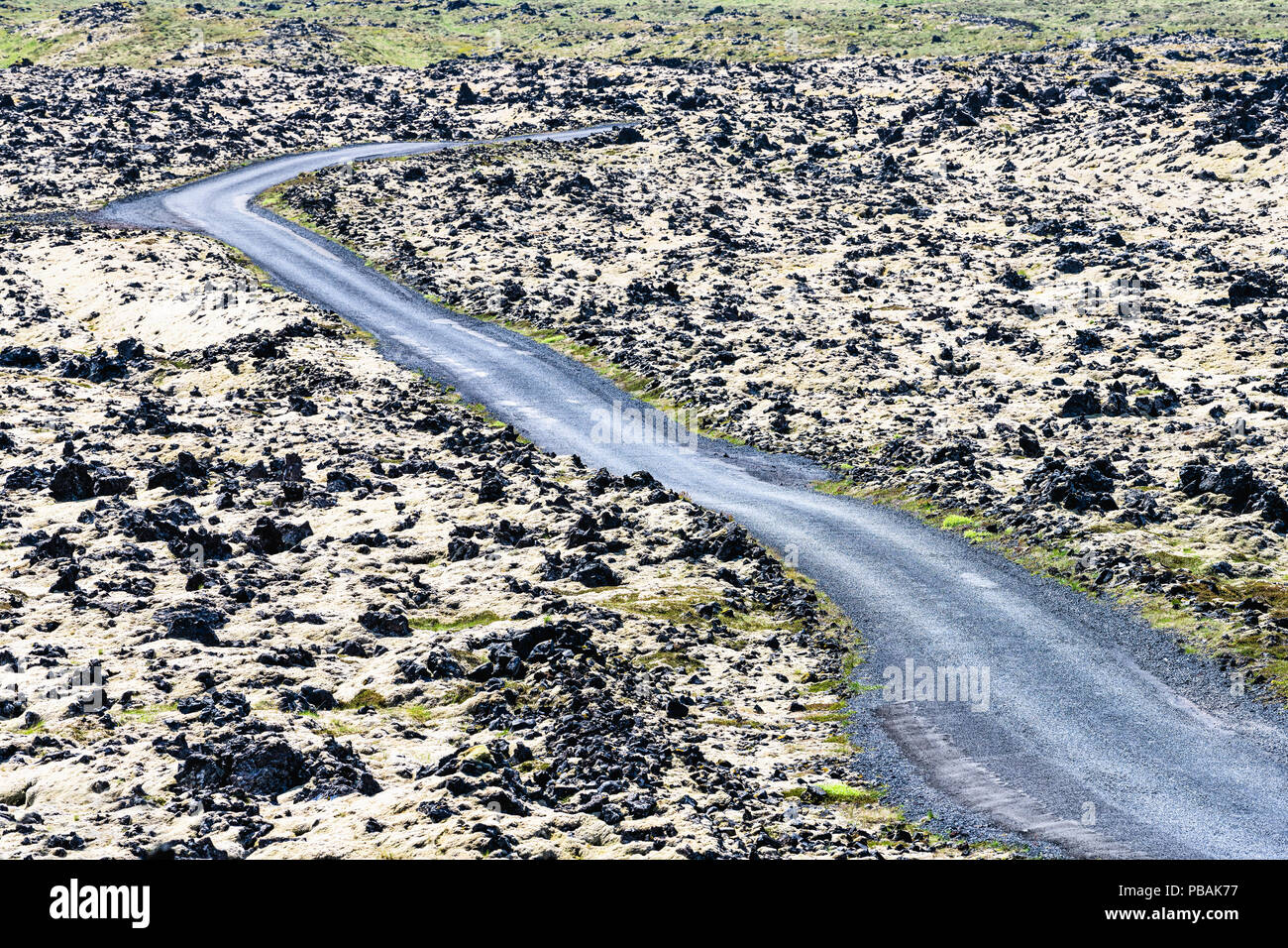 Winding, disappearing road in black lava field formations to Djupalonssandur beach at Snaefellsnes peninsula, Iceland - Stock Image