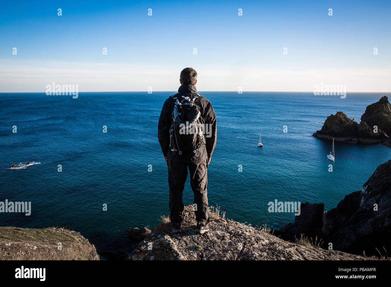 A rear view of a male backpacker or hiker standing on a high cliff and admiring an awe inspiring sea view Stock Photo