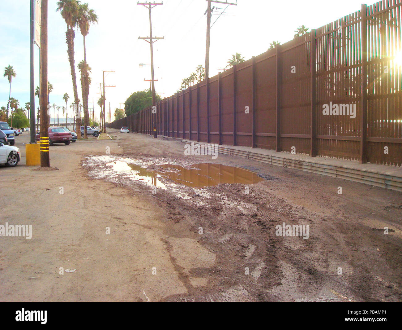 Sun breaking through the border fence between Calexico, California, United States and Mexicali, Baja California, Mexico in 2010. Stock Photo