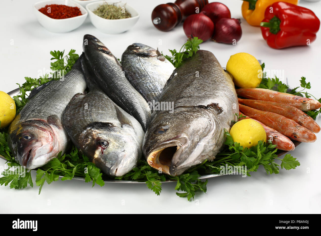 assortment of raw fishes on plate - Stock Image