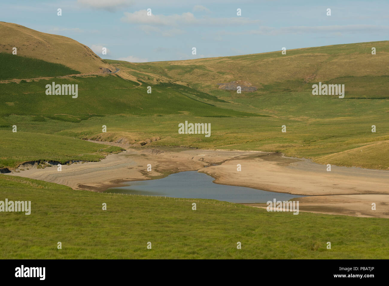 Summer heatwave 2018: Very low water levels at in the Craig Goch reservoir, the upper part of The Elan Valley system, Powys , Mid Wales UK. The Elan Valley system of dams and reservoirs supplies 133 billion litres of water a year via a gravity fed pipeline to Birmingham - Stock Image