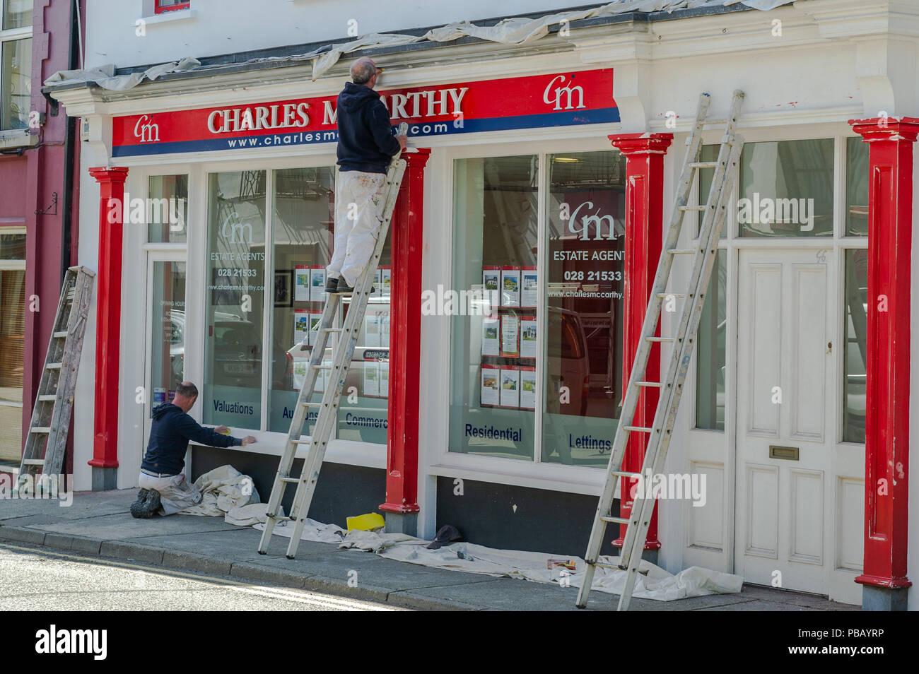 Painters and decorators repaint the front of an Estate Agents/Realtors in Skibbereen, West Cork, Ireland on a summer's day. - Stock Image