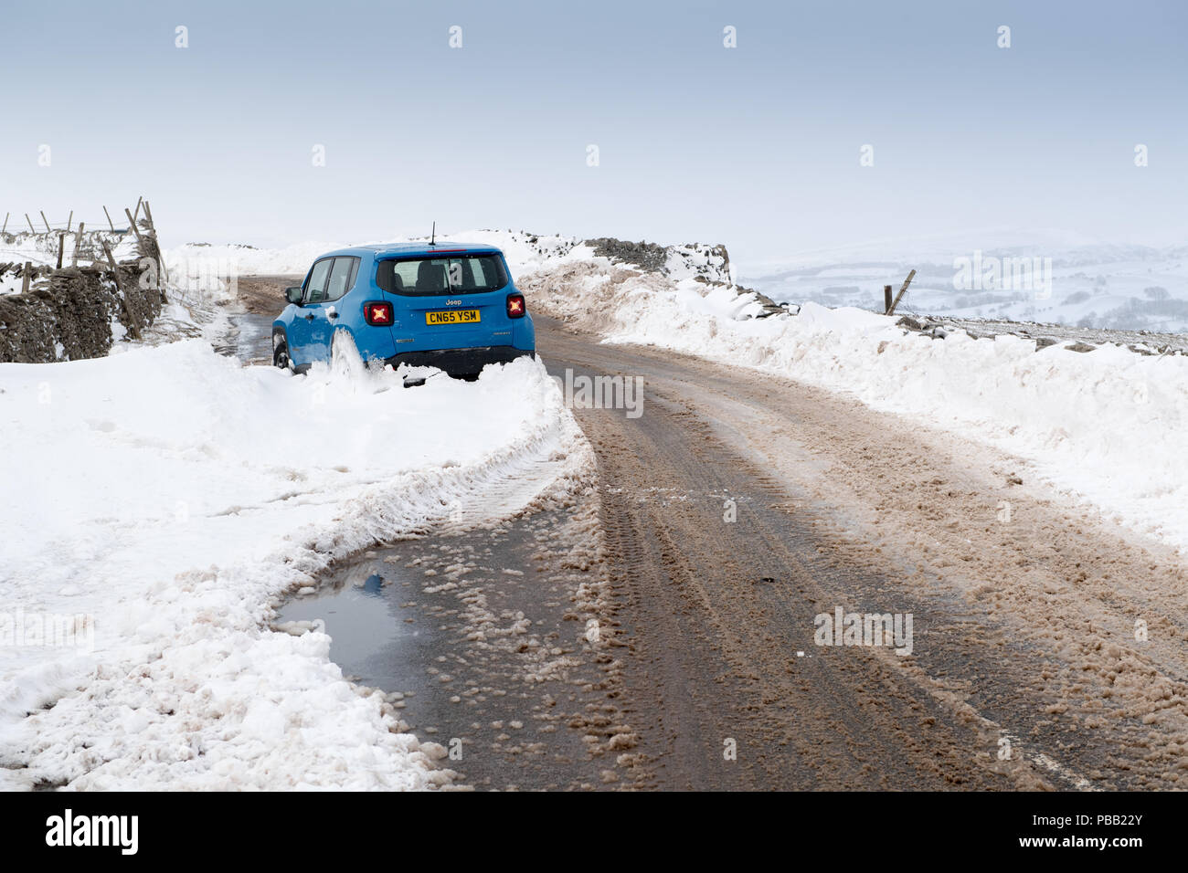 Car abandoned in a snowdrift on a rural road in Cumbria, after a snowstorm. - Stock Image