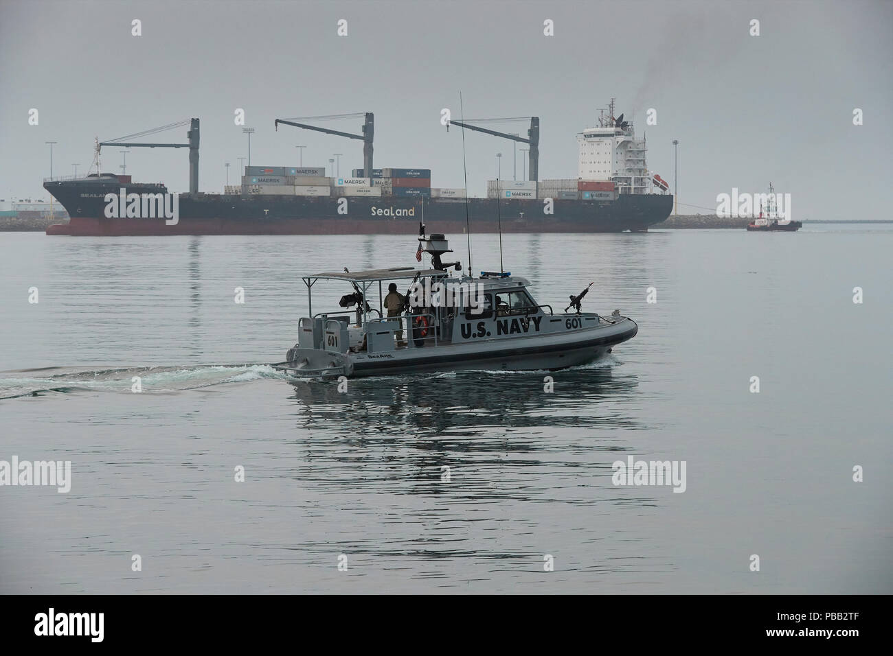 U.S. Navy Patrol Boat, Patrols The Port Of Los Angeles, An Arriving SeaLand Container Ship Behind. California, USA. - Stock Image