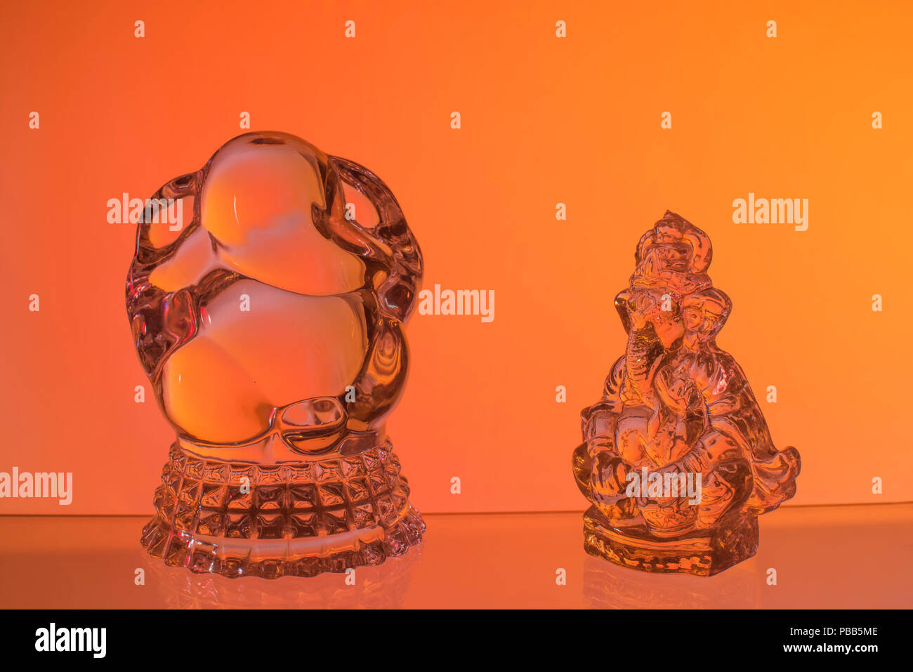 Two idols of Lord Ganesh the divine elephant-headed Hindu Gods made of glass and worshiped by Indian people kept against red orange yellow background - Stock Image