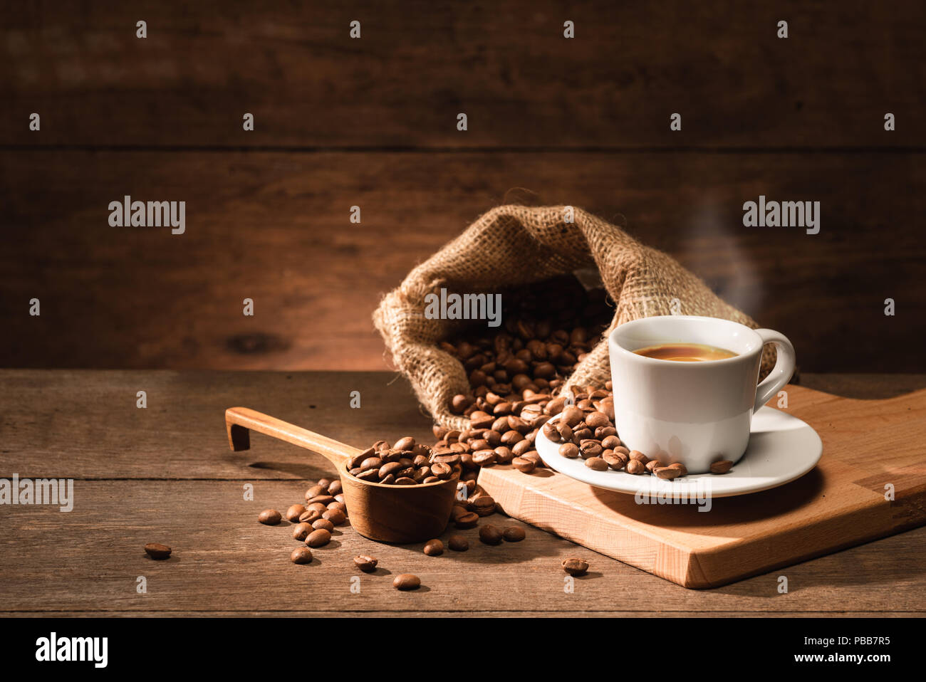 A shot of espresso with roasted coffee bean bag and wooden spoon - Stock Image