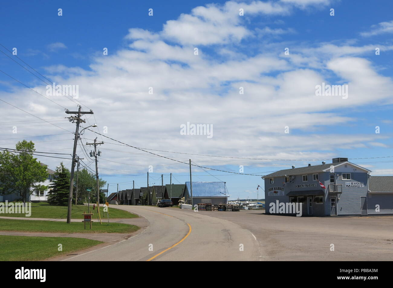 A view along Harbourview Drive towards Doiron Fisheries, with boats in the background at North Rustico, a thriving fish market business on PEI - Stock Image