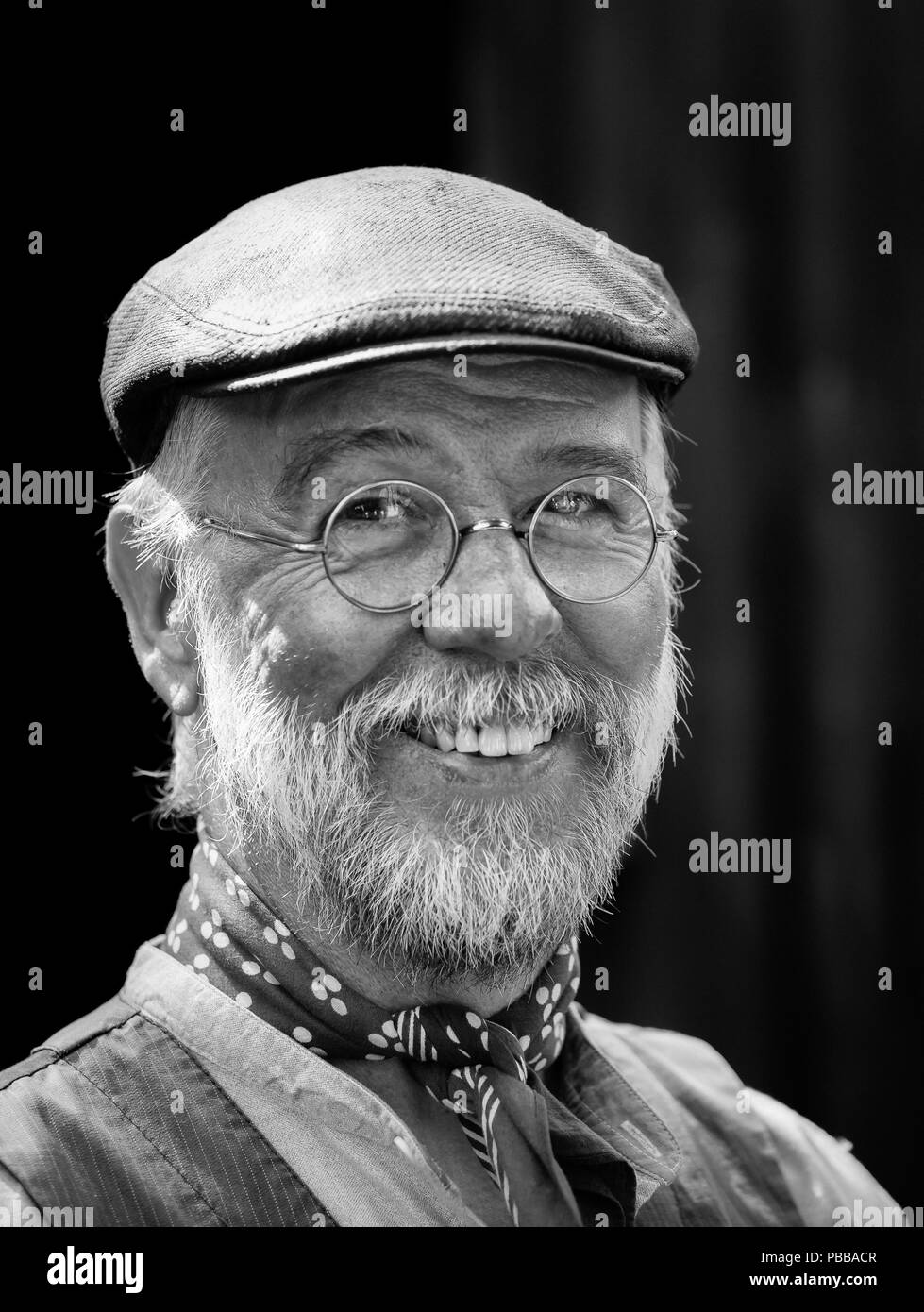 Close-up, black and white portrait of smiling colliery worker at the Black Country Living Museum, Dudley during the 1940s weekend event, July 2018. - Stock Image