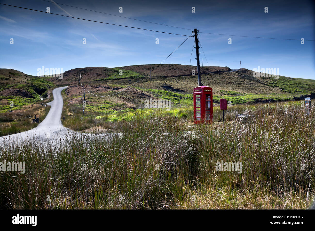Red telephone box and mail box on isolated minor road near Tregaron, Wales, UK - Stock Image