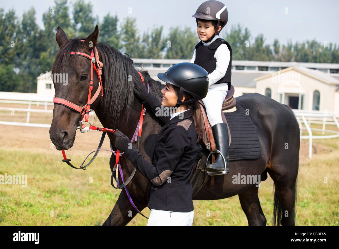 Young Chinese Mother Teaching Daughter Riding Horse Stock Photo Alamy