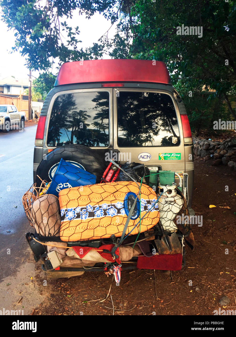 A van with all the essentials needed for a day at the beach or longer stay  is parked outside Charley Young beach, S.Kihei, Maui, USA. - Stock Image