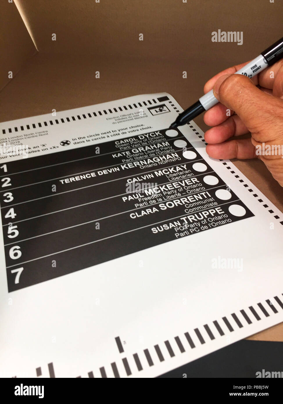 Seven candidates: A voter about to mark the ballot with a sharpie inside a polling booth, Ontario, Canada.  To be scanned and counted electronically. - Stock Image