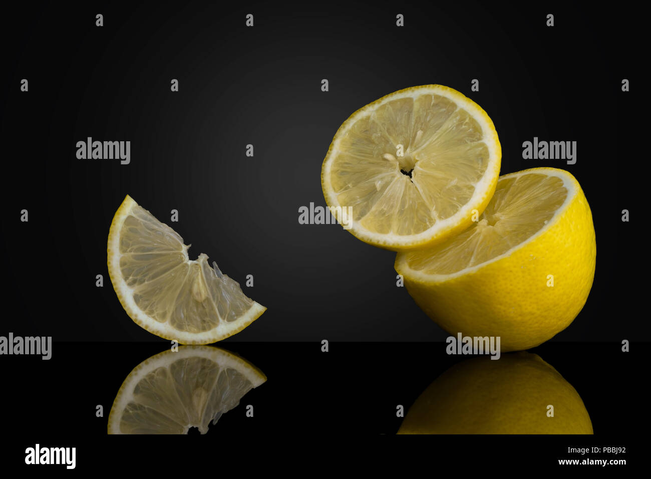 Gravity defying fresh lemon slices, pieces on dark background. Unusual artistic photo. - Stock Image