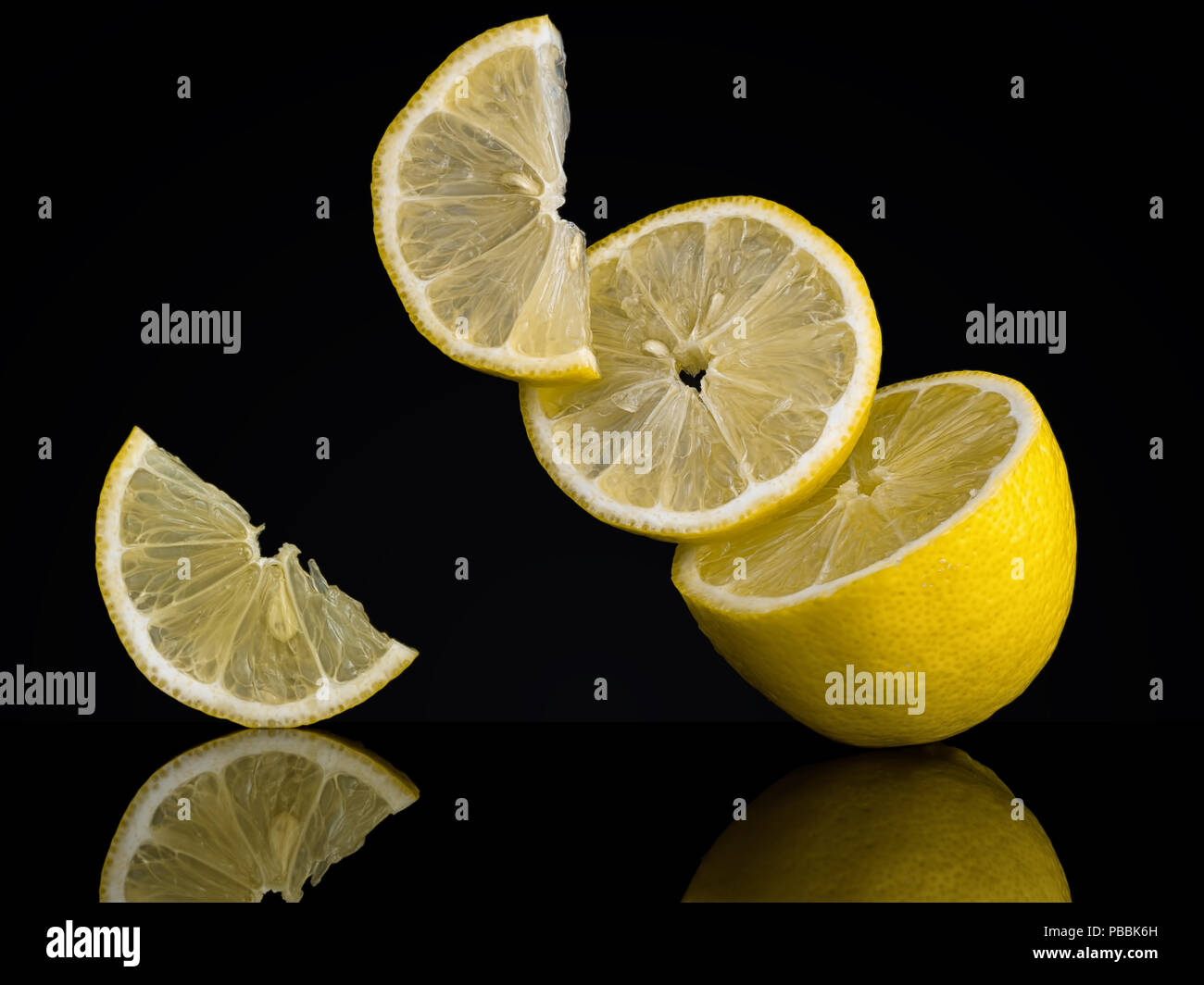 Lemon slices, pieces on a black background. Unusual photo. Seem to defy gravity  - Stock Image