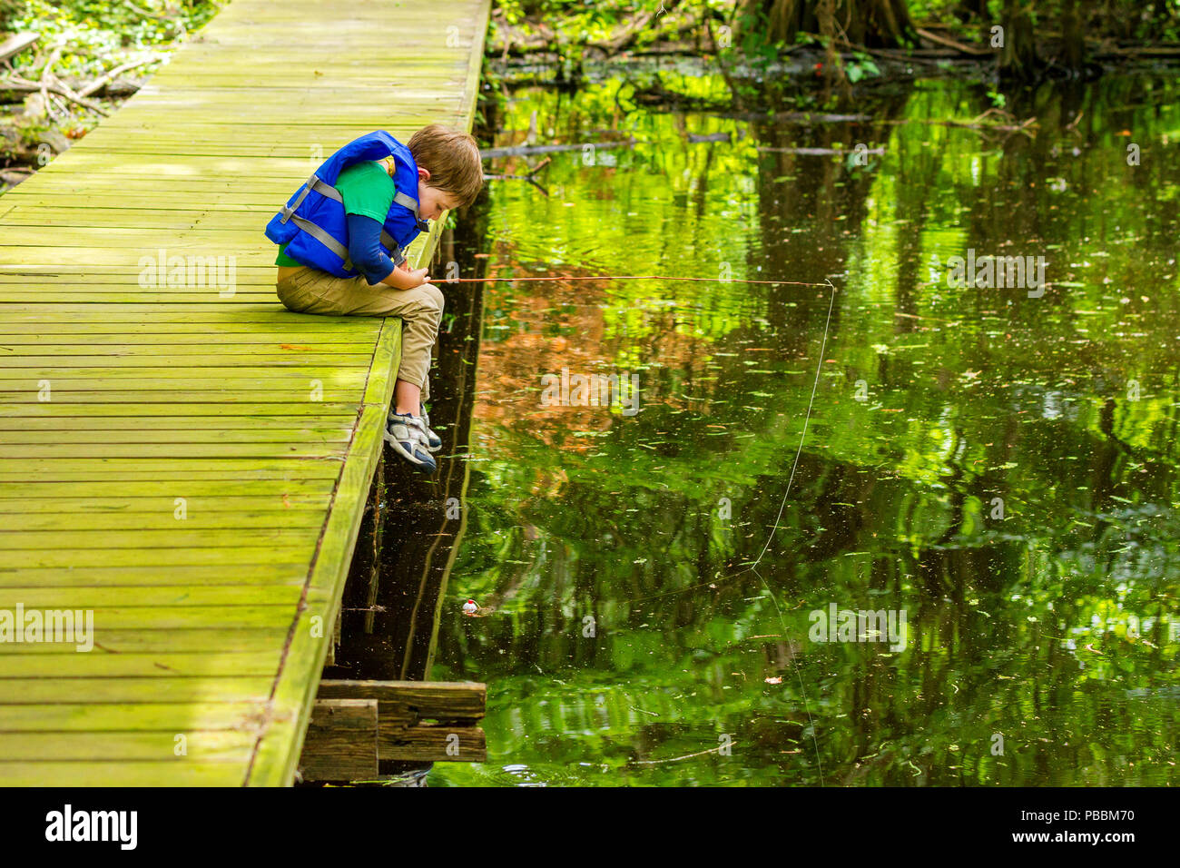 An impatient young, fishing boy stares at his still bobber, willing it to move, as he leans over the edge of the dock he is fishing from at Lake Bisti - Stock Image
