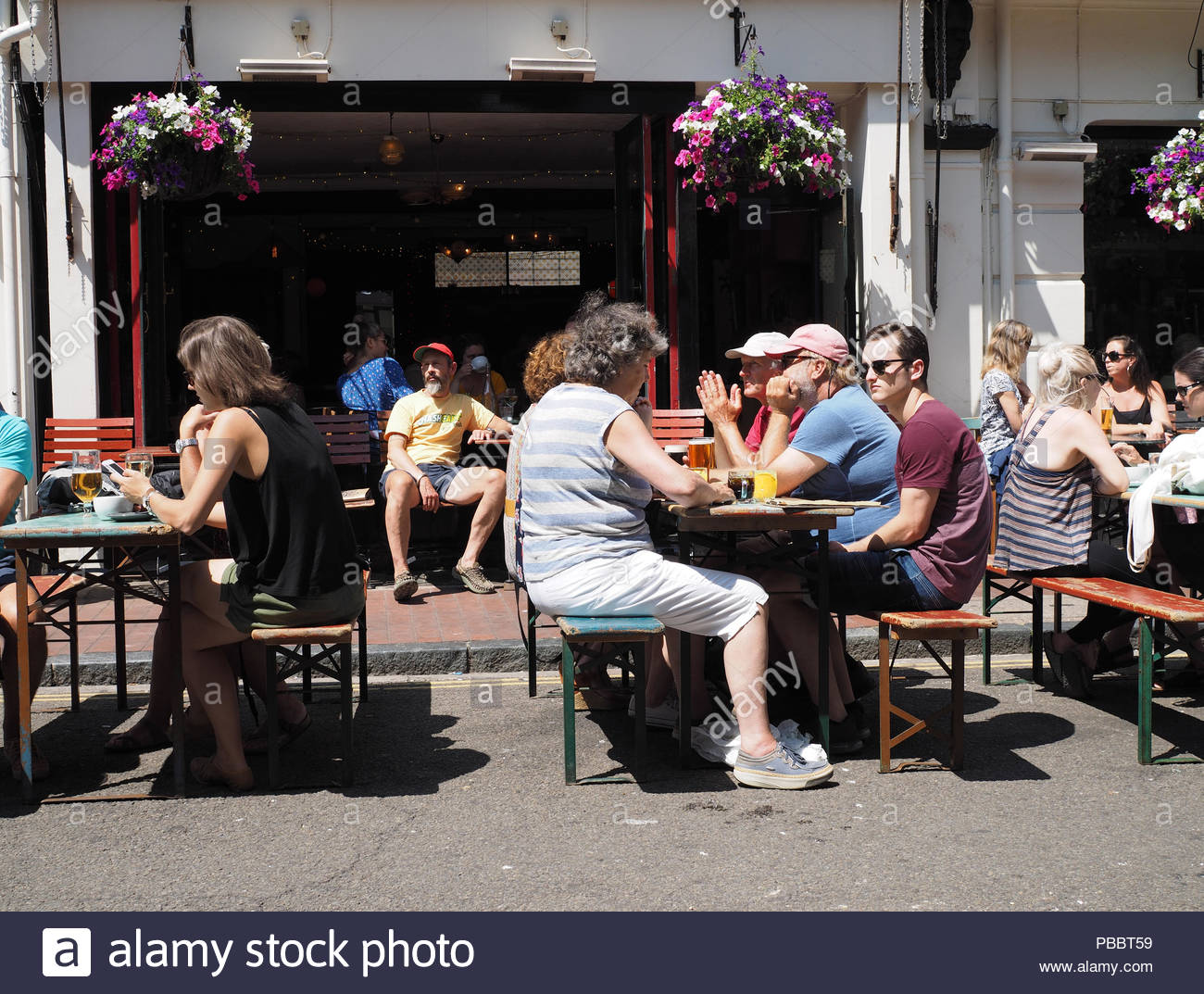 People sitting at pavement tables in the hot sunshine, Brighton Lanes, England, UK, Summer 2018 - Stock Image