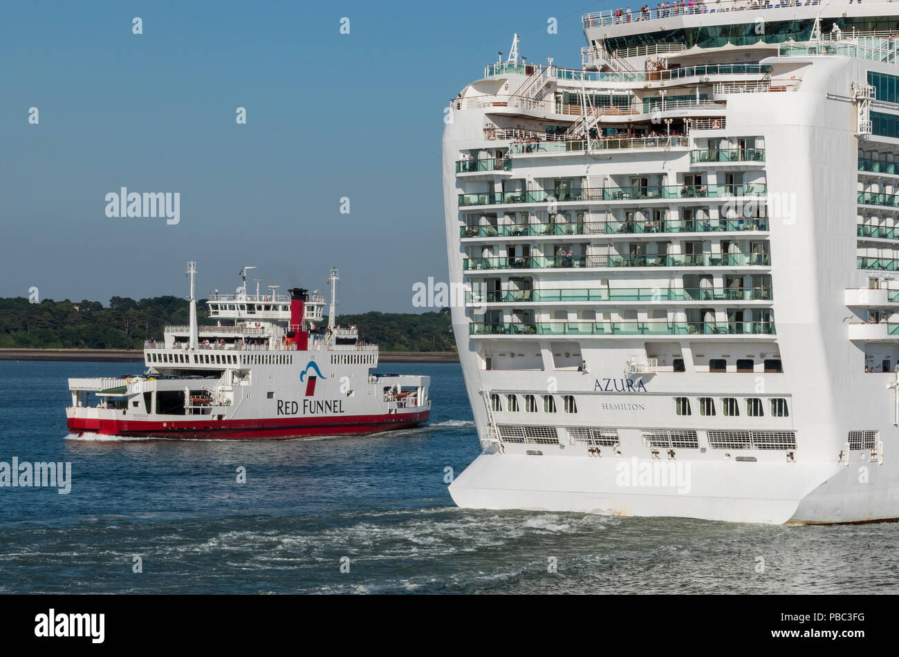 the isle of wight ferry passing the giant p and o cruise liner azura in Southampton water southampton docks in the port of Southampton. - Stock Image