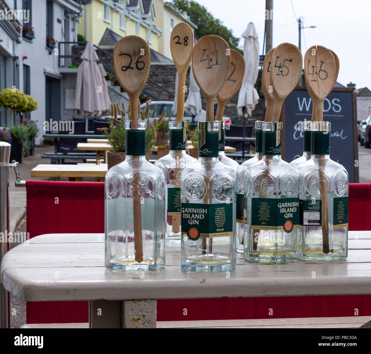Empty Gin Bottles With Numbered Wooden Spoons Being Used For Table - Restaurant table markers