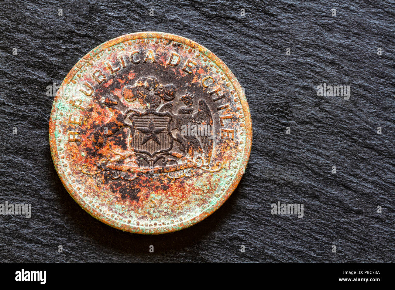 Corroded coin of 100 Chilean pesos from 1981. - Stock Image