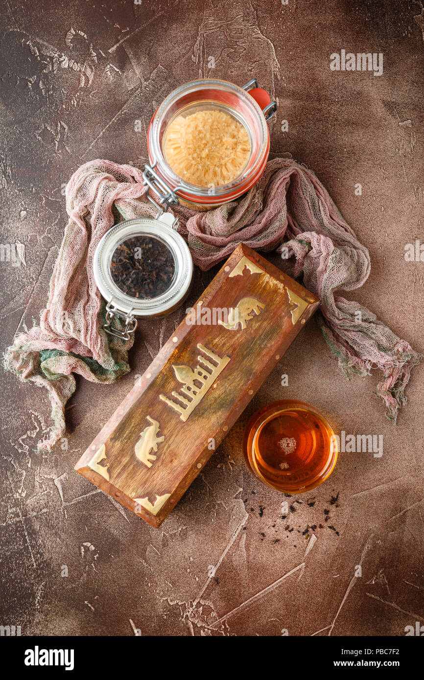 Glass cup of hot tea with jars of different kinds of tea - black, green, herbal and wooden box for tea Stock Photo