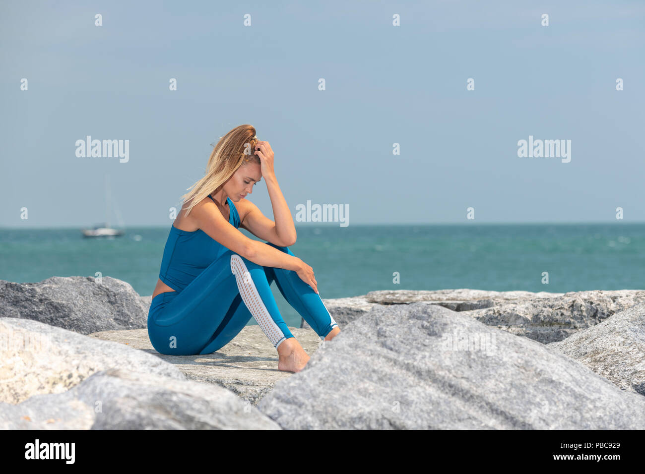 fit sports woman exhausted after exercise sitting on rocks by the sea with her head in her hands - Stock Image