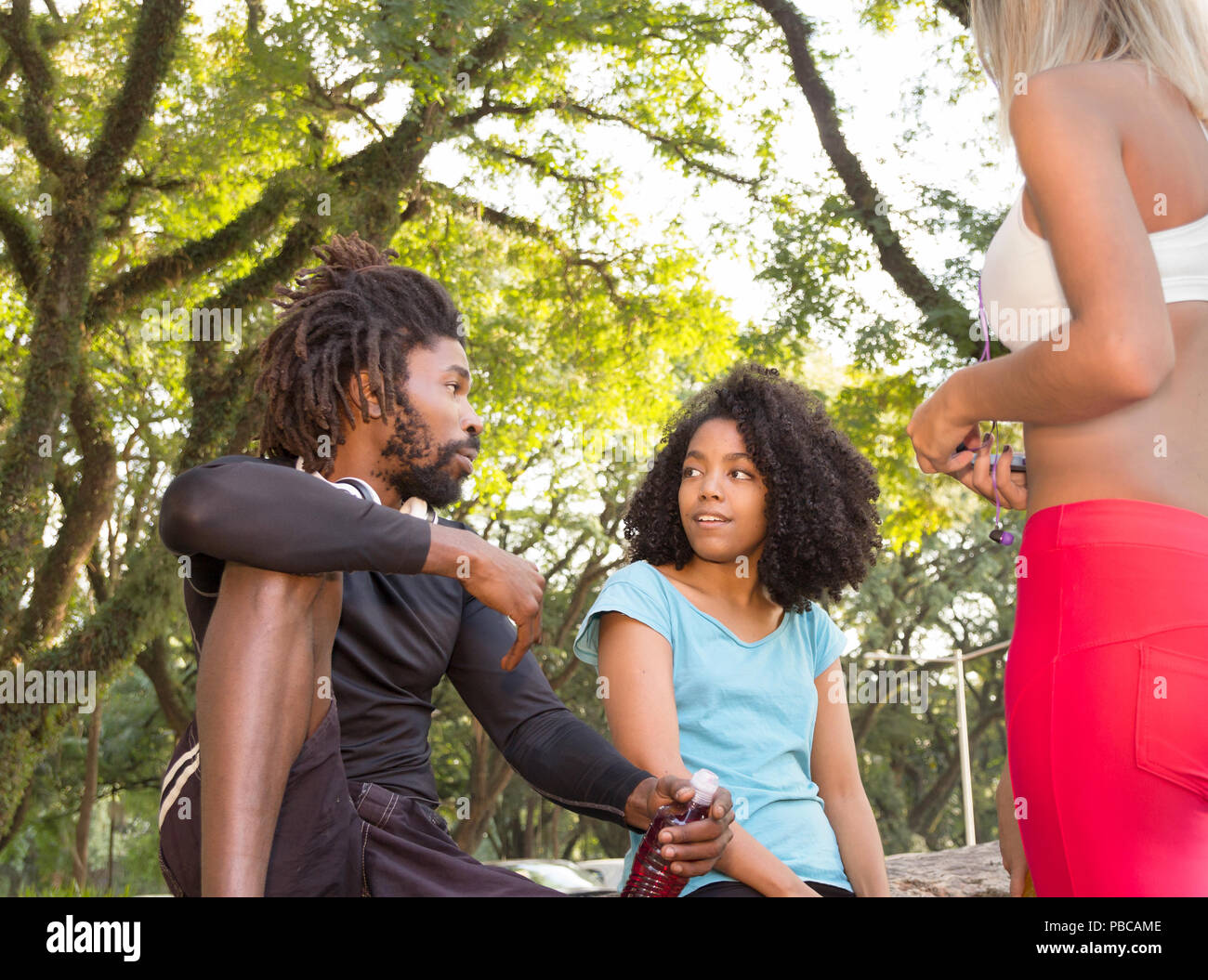 Group of athletes sitting on a tree and talking. Candid and unposed. Friends enjoying outdoors in woodland. Healthy lifestyle and sport concept. - Stock Image