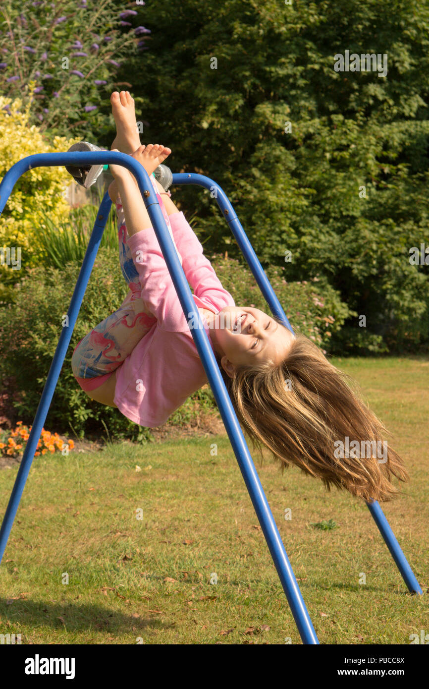 six year old girl doing gymnastics acrobatics on apparatus in back garden for play, UK. Stock Photo