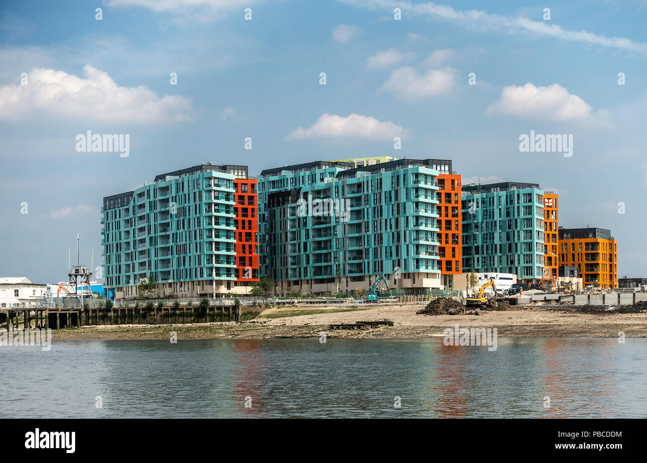 New blocks of flats with balconies on the side of the River Thames near Morden Wharf, Greenwich peninsula, London. Construction work going on. - Stock Image