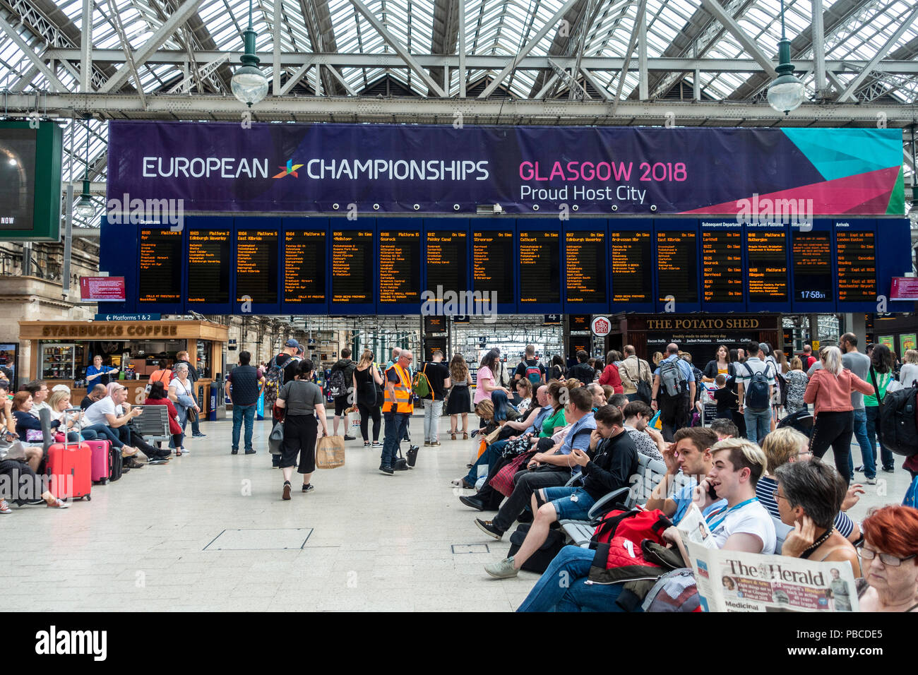 Large Banner promoting Glasgow 2018, the multi-sport European Championships, above the departures board in Glasgow Central Station, Scotland, UK - Stock Image
