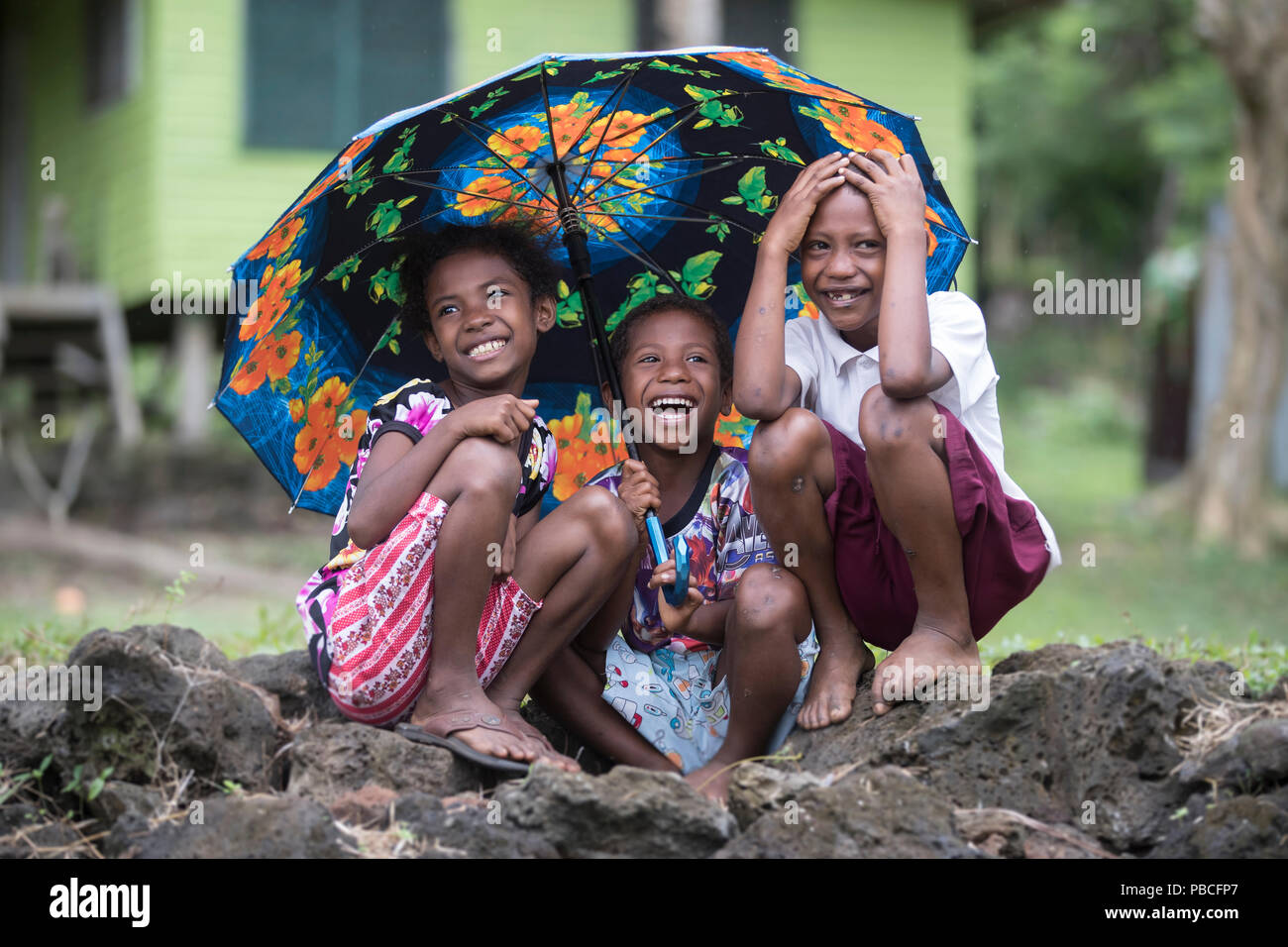 Three children sitting under an umbrella laughing together - Papua New Guinea - Stock Image