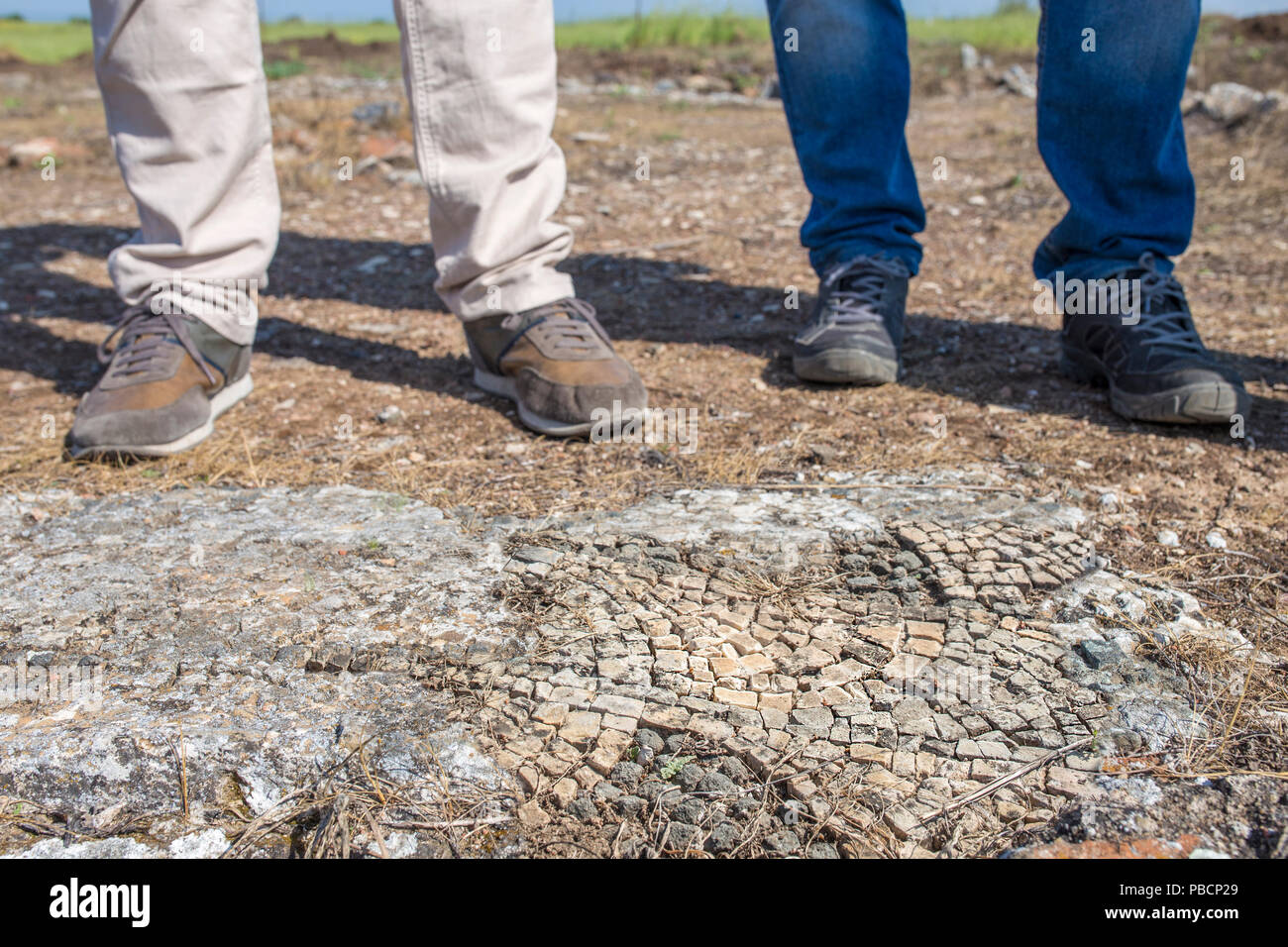 Archeological site supervisors feet. Ancient Mosaic on the forefront - Stock Image