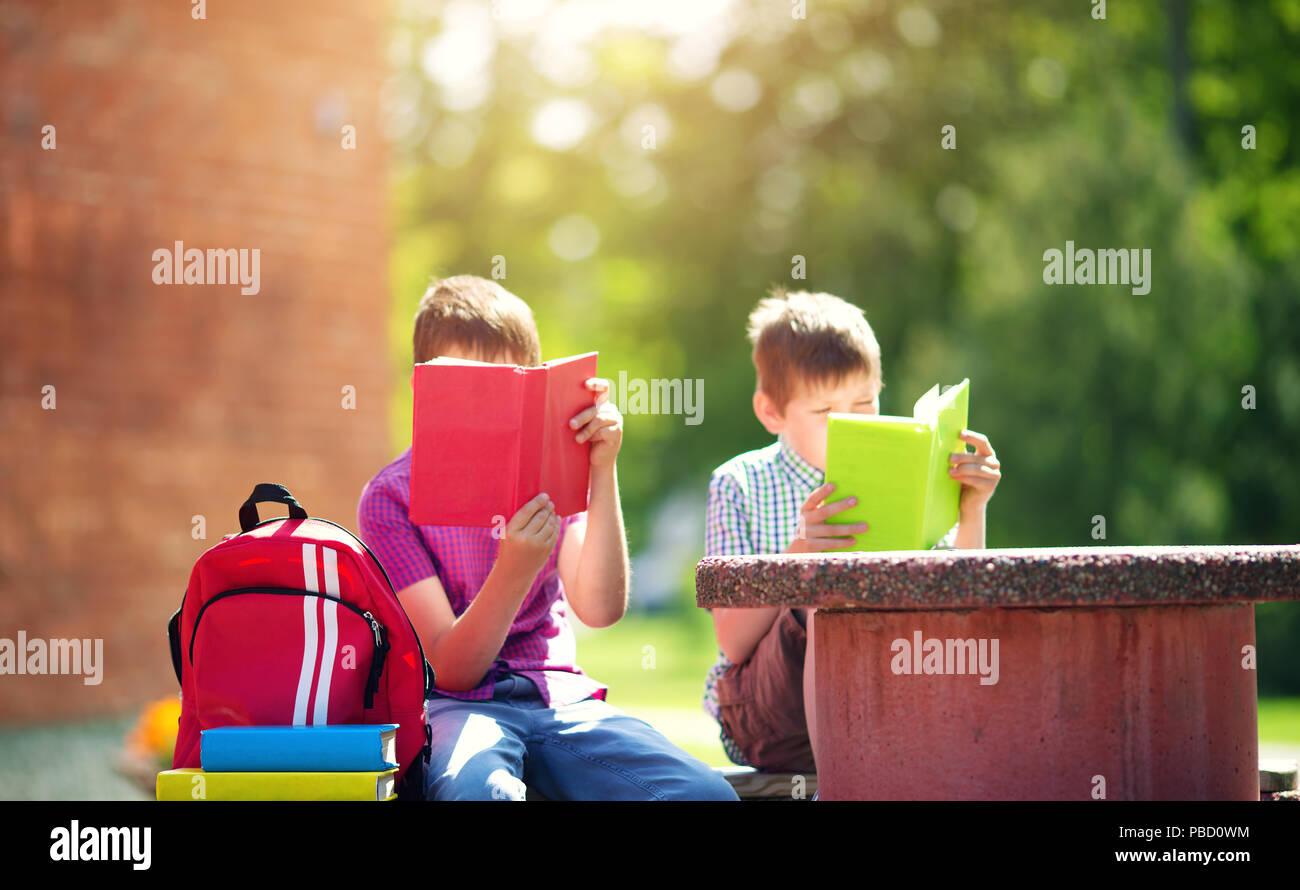 Children with rucksacks standing in the park near school - Stock Image