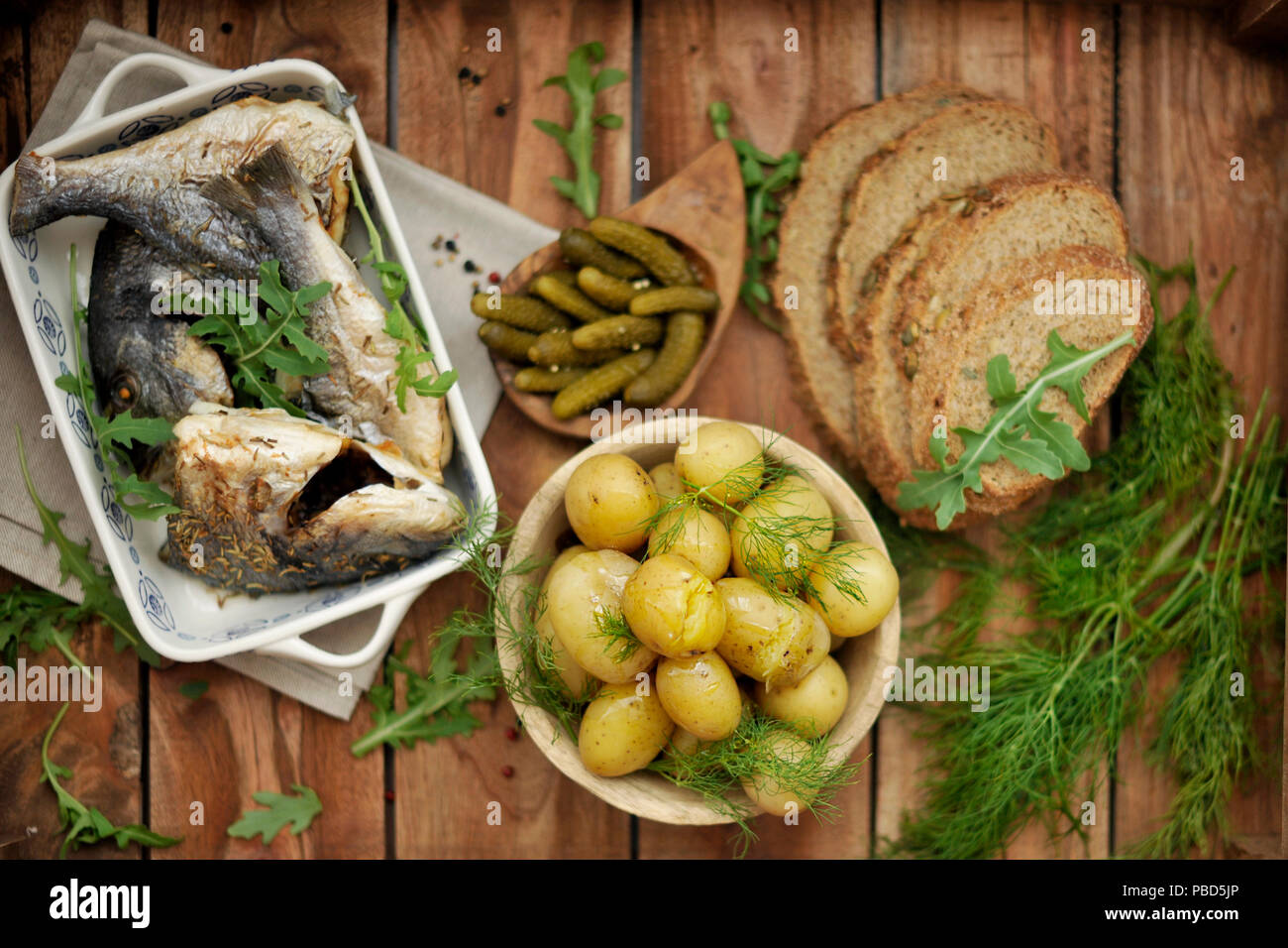 lunch. baked dorado and young potatoes. Marinated cucumbers and black bread. in rustic style, - Stock Image