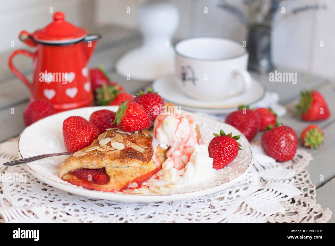 Sweet homemade pastries for breakfast. With strawberry filling and ice cream. Morning coffee. Red jug with milk. milkman. A cup of tea. family breakfast. Photo in white colors - Stock Image