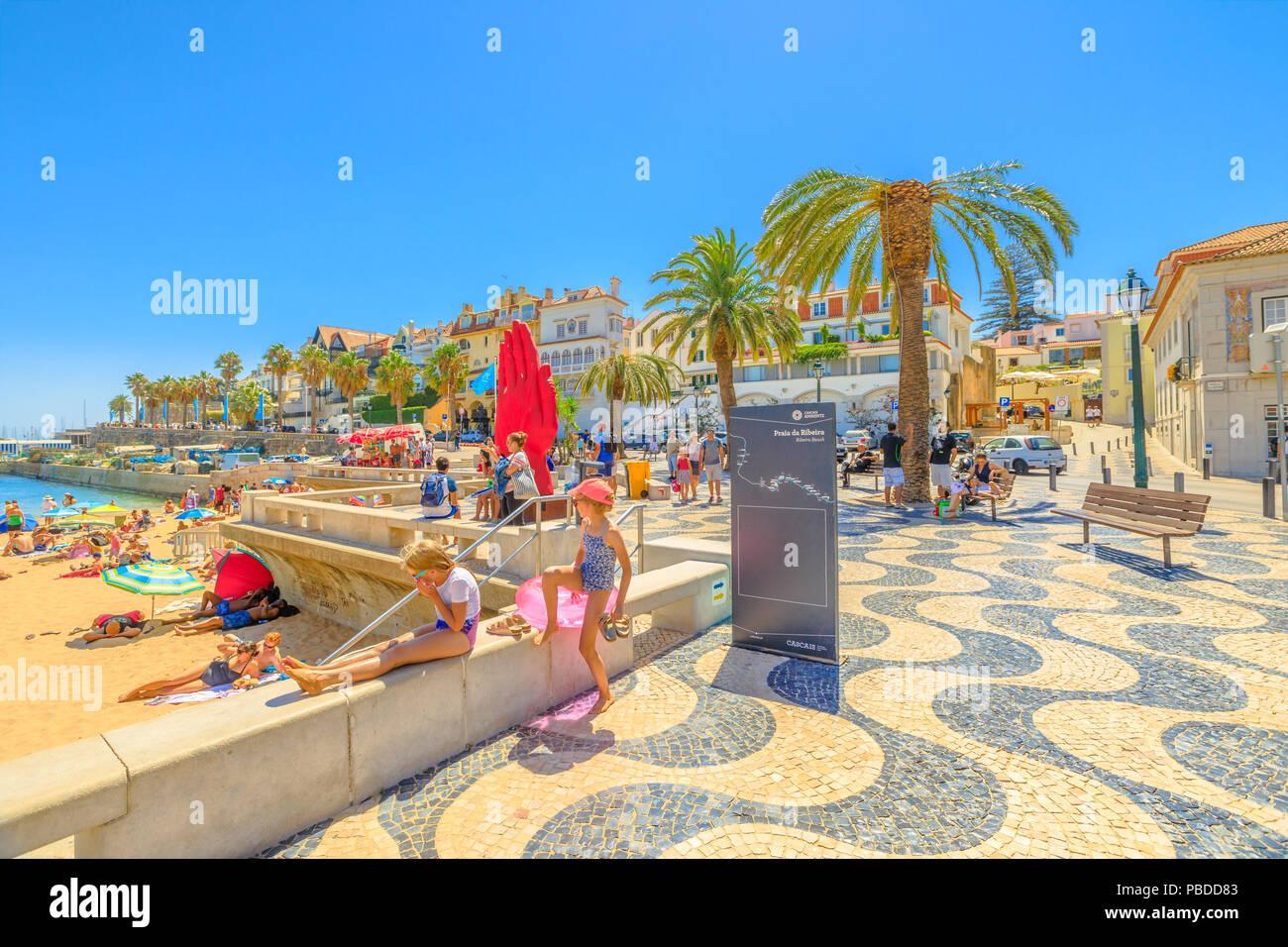 Cascais, Portugal - August 6, 2017: promenade along Ribeira beach on Passeio Dom Luis I street. Cascais is popular summer vacation spot in Lisbon Coas - Stock Image