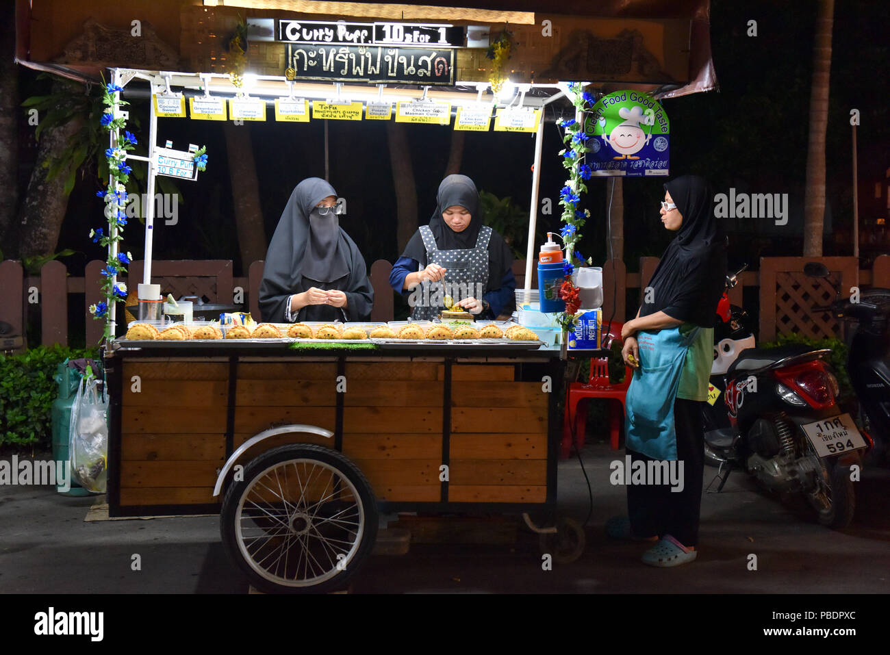 Muslim Thai women running a food stall in Pai, Northern Thailand - Stock Image